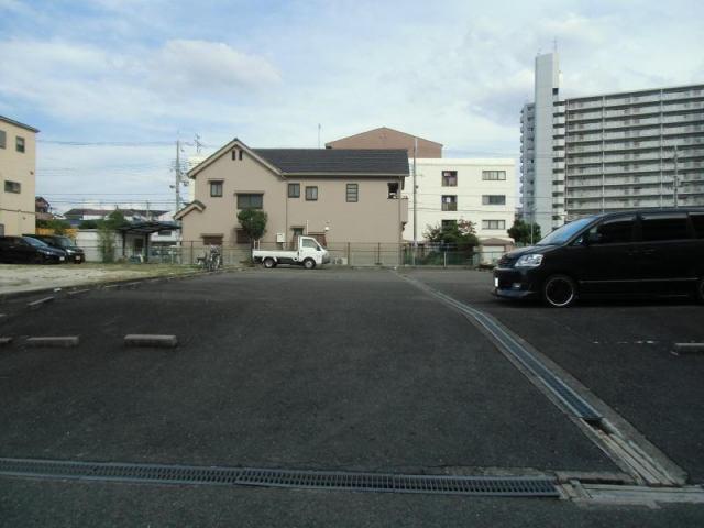アスファルト舗装と砂利の地面がある駐車場です。